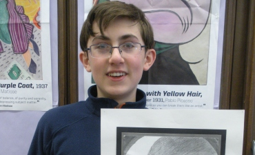Student holds art work