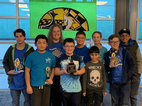 Chess club students hold trophy