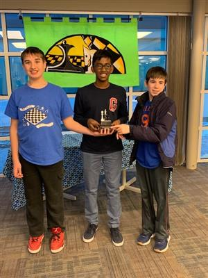 Three students hold chess trophy