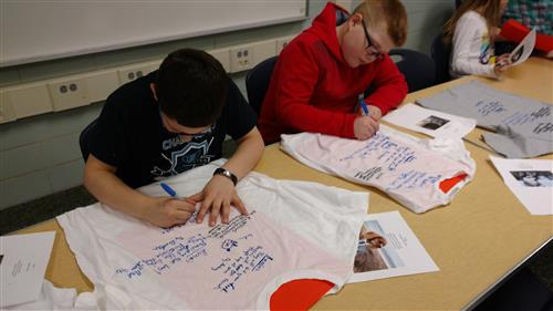 Students write poems on shirts with markers
