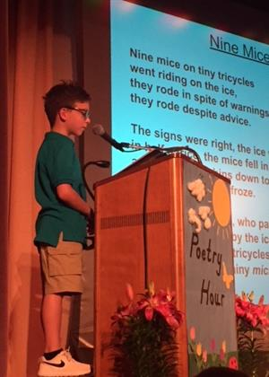Student reads poetry at podium