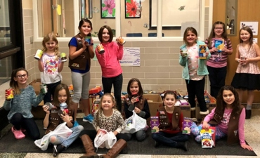 Elementary girl scouts with food they collected