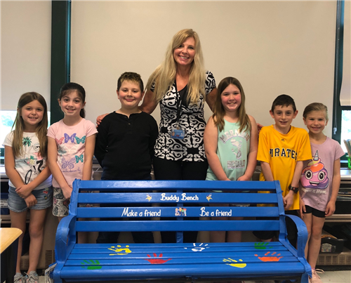 Teacher and students stand by bench