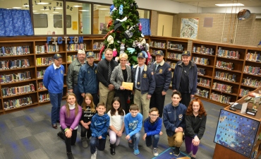 Middle School staff and students stand by Christmas tree