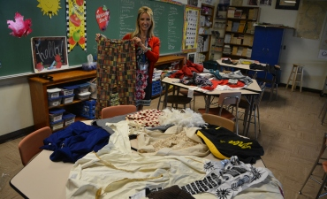 Teacher holds vintage clothing from 1960s
