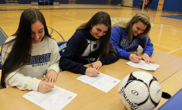 Three female soccer plays sign letters of intent to play collegiate sports